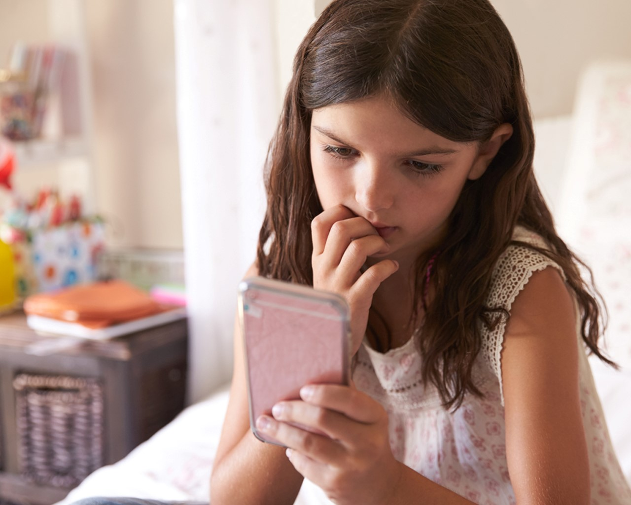 A child views her mobile phone with a worried expression