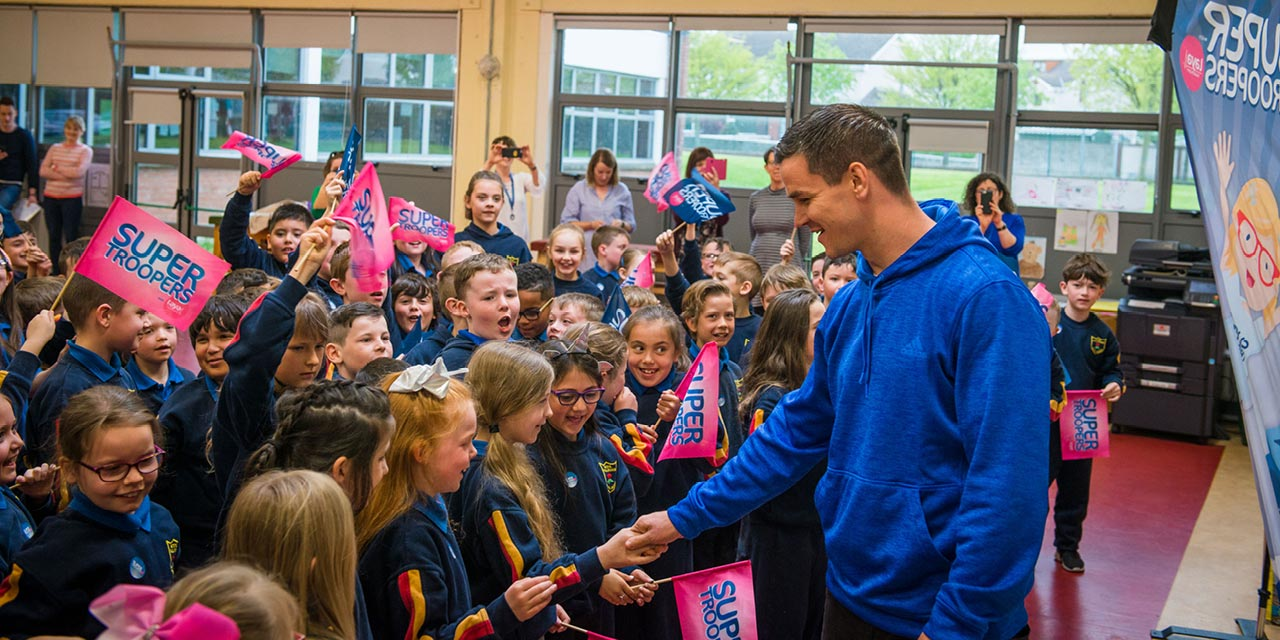 Johnny Sexton is greeted by a group of flag waving children in Scoil Maelruain, Tallaght.