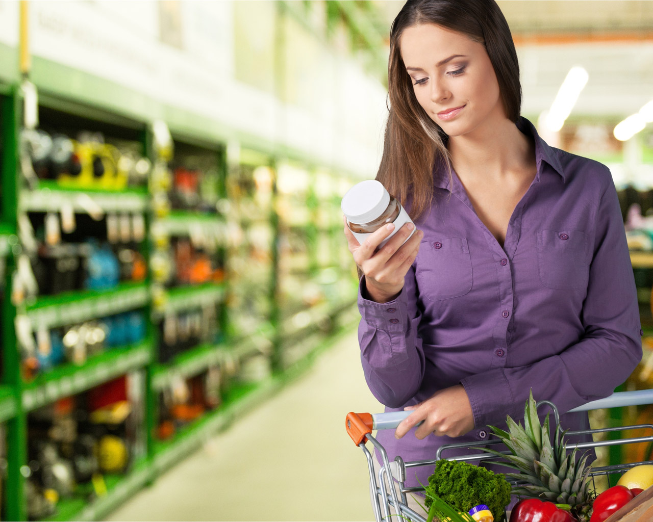 Woman in purple shirt reading label of food product in supermarket