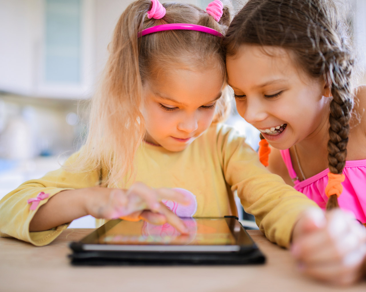 Two children play happily on a tablet