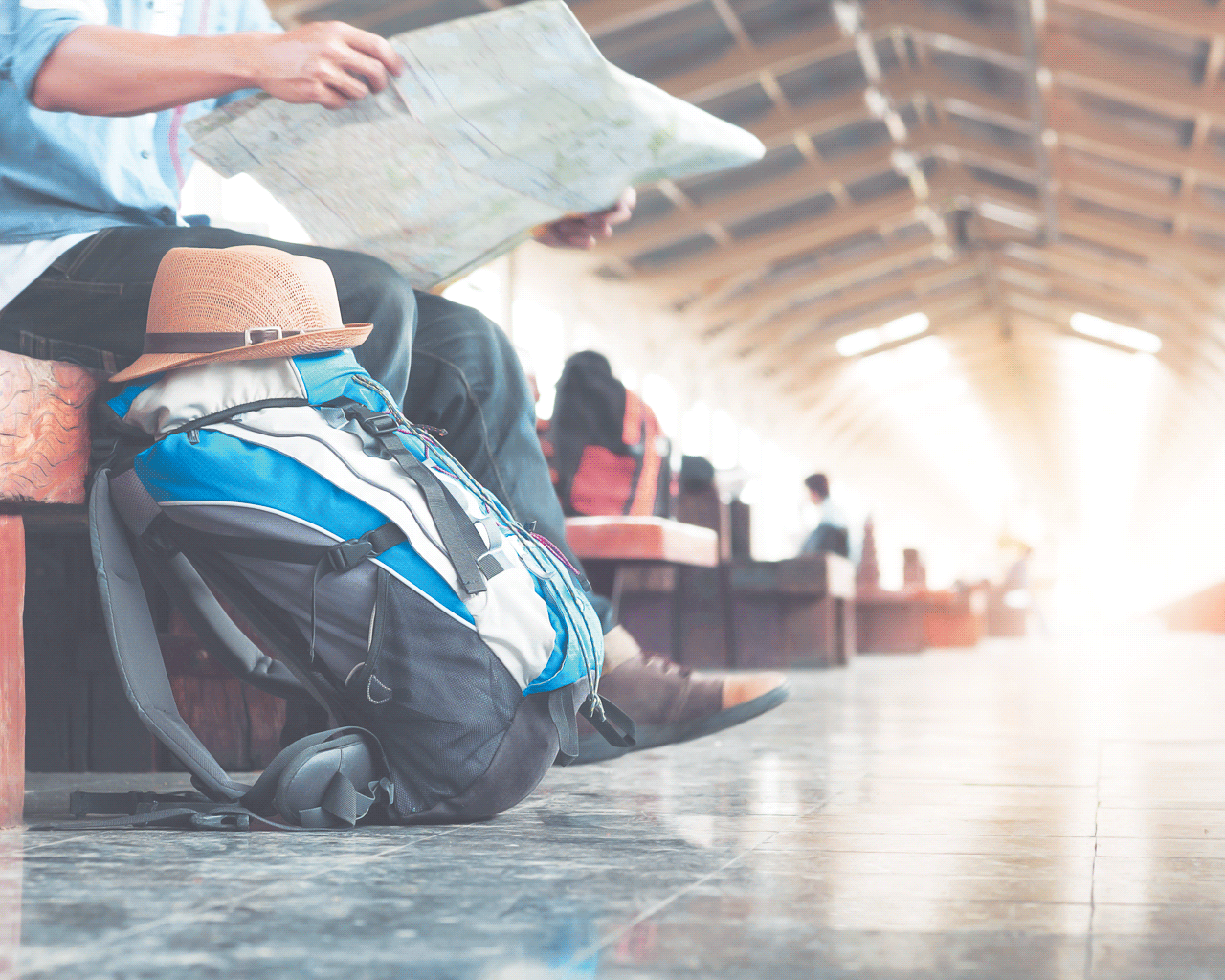 Image of backpacker waiting in train station, reading map