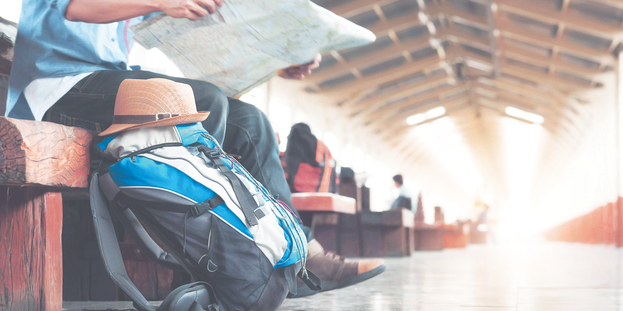 Image of backpacker waiting in a station, reading a map