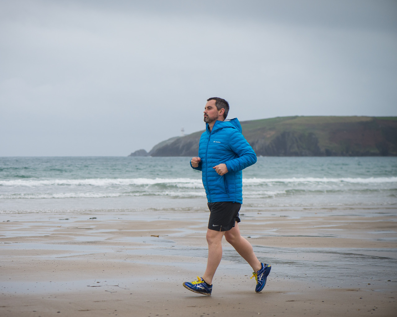 Karl Henry in a blue top, running on a beach