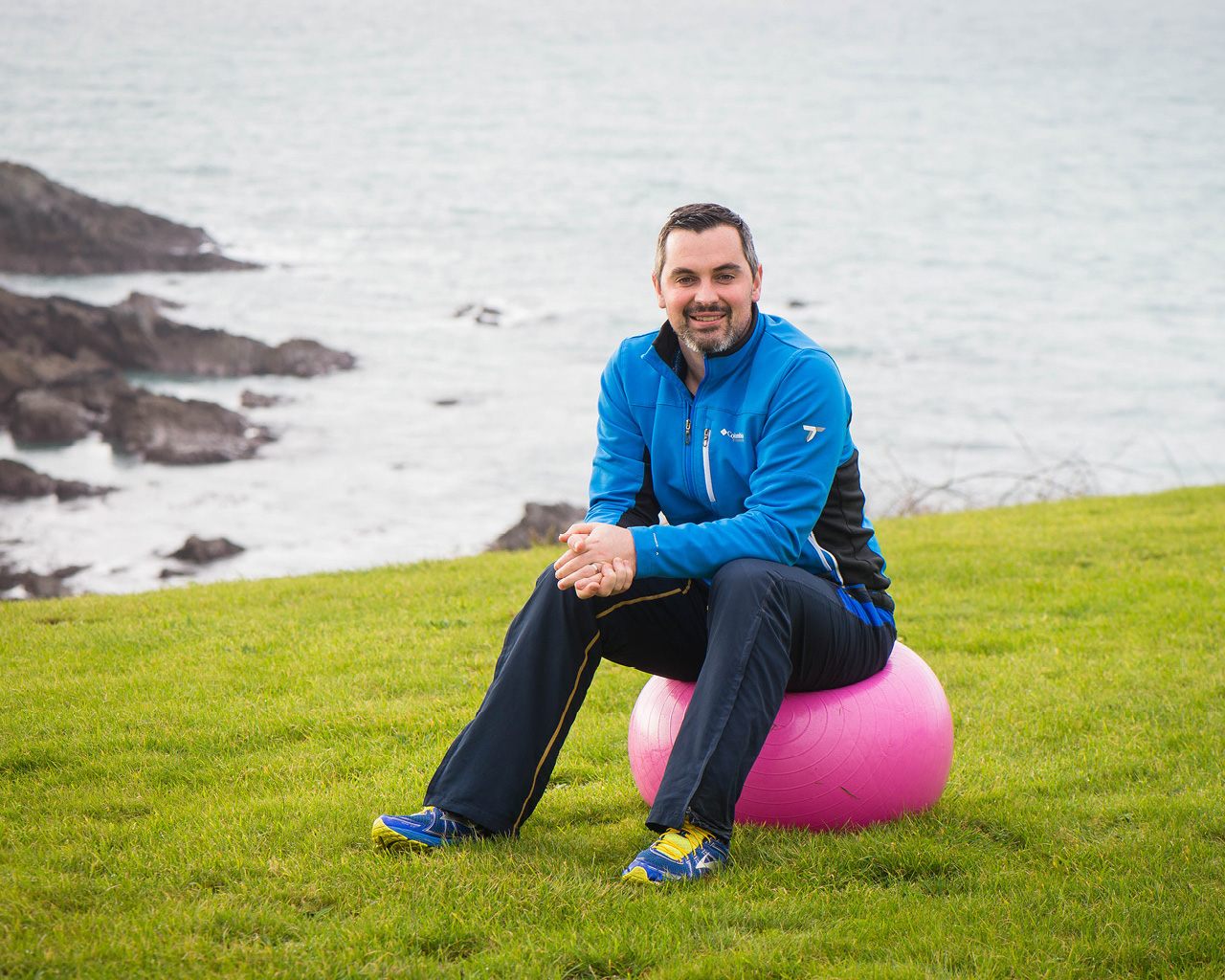 Karl Henry sitting on exercise in a scenic, beachside setting