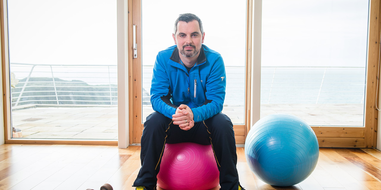 Karl Henry in a blue top, sitting on a pink exercise ball